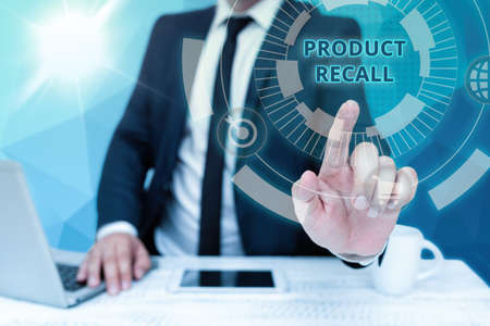 Handwriting text Product Recall. Word Written on request to return the possible product issues to the market Bussiness Man Sitting Desk Laptop And Phone Pointing Futuristic Technology. Foto de archivo