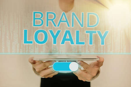 Writing displaying text Brand Loyalty. Word Written on positive feelings to a brand and purchase the same product Lady In Uniform Standing Holding Tablet Showing Futuristic Technologies. Stockfoto