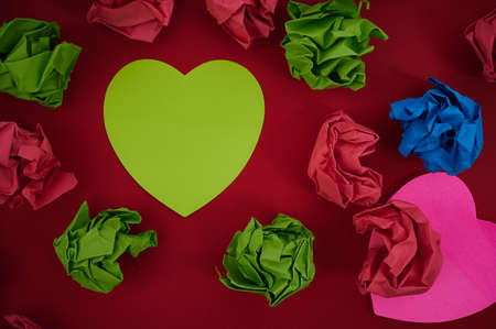 Colorful Crumpled Papers Circular Pattern Surrounding Heart Shaped Card. Blank Note Within The Flashy Pieces Of Paper Balls Arranged In A Circle.