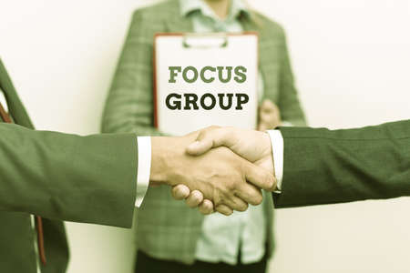Text sign showing Focus Group. Business approach consist of carefullyselected participants to provide feedback Two Professional Well-Dressed Corporate Businessmen Handshake Indoors