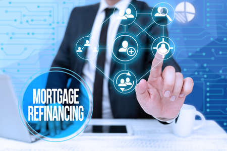 Hand writing sign Mortgage Refinancing. Business showcase process of replacement of an existing debt obligation Bussiness Man Sitting Desk Laptop And Phone Pointing Futuristic Technology. Standard-Bild