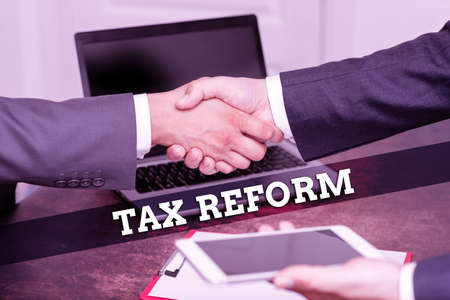 Hand writing sign Tax Reform. Business showcase government policy about the collection of taxes with business owners Two Professional Well-Dressed Corporate Businessmen Handshake Indoors