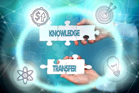 Writing displaying text Knowledge Transfer. Business approach sharing or disseminating of knowledge and experience Hand Holding Jigsaw Puzzle Piece Unlocking New Futuristic Technologies.