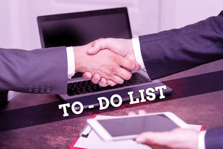 Hand writing sign To do List, Word Written on a list of tasks to complete and organize according to priority Two Professional Well-Dressed Corporate Businessmen Handshake Indoors Standard-Bild