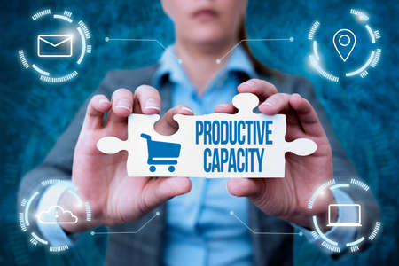Conceptual display Productive Capacity. Business concept the maximum possible output of a production plant Business Woman Holding Jigsaw Puzzle Piece Unlocking New Futuristic Tech. Banque d'images