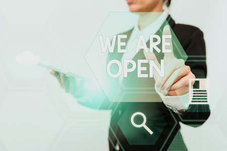 Text sign showing We Are Open. Business concept no enclosing or confining barrier, accessible on all sides Woman In Suit Holding Tablet Showing Futuristic Interface Display. Archivio Fotografico