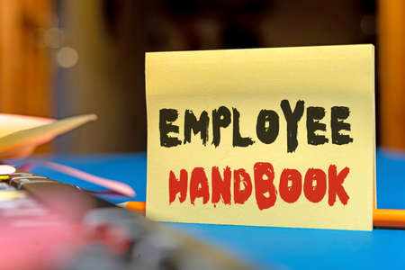 Text caption presenting Employee Handbook. Business idea states the rules and regulations and policies of a company Multiple Assorted Collection Office Stationery Photo Placed Over Table