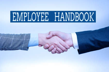 Inspiration showing sign Employee Handbook. Internet Concept states the rules and regulations and policies of a company Two Professional Well-Dressed Corporate Businessmen Handshake Indoors