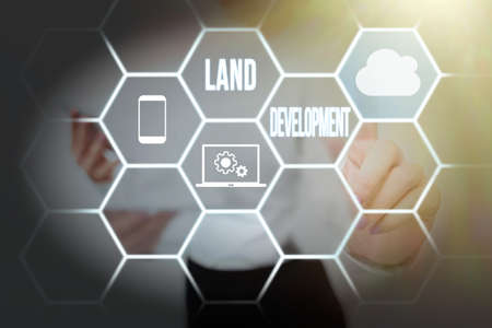 Hand writing sign Land Development. Word Written on process of acquiring land for constructing infrastructures Lady Holding Tablet Pressing On Virtual Button Showing Futuristic Tech.