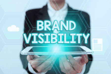 Text sign showing Brand Visibility. Business showcase frequency at which showing see your brand in search results Lady In Uniform Holding Touchpad Showing Futuristic Virtual Interface. Banque d'images
