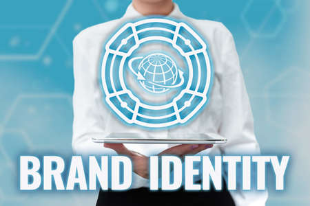 Writing displaying text Brand Identity. Business concept visible elements of a brand that identify and distinguish Lady Uniform Standing Tablet Hand Presenting Virtual Modern Technology