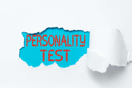 Conceptual caption Personality Test. Word for A method of assessing human personality constructs Tear on sheet reveals background behind the front side