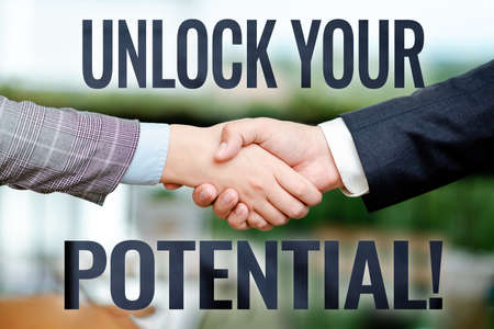 Text sign showing Unlock Your Potential. Conceptual photo release possibilities Education and good training is key Two Professional Well-Dressed Corporate Businessmen Handshake Indoors