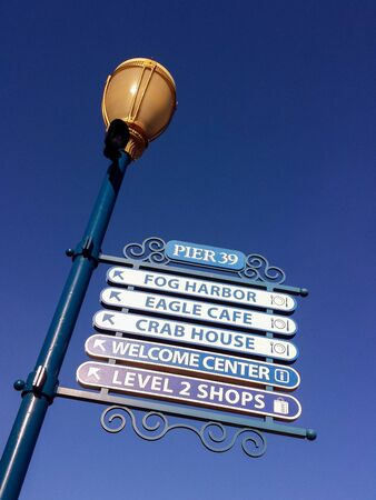 Pier 39 sign pointing to various restaurants, San Francisco, USA with Street Lamp and blue sky Stockfoto