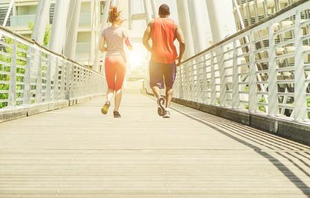 Deux jeunes athlètes qui font du jogging dans une zone de compétition urbaine en plein air - Les coureurs s'entraînent à l'extérieur - Courir pour un concept de mode de vie sportif et sportif - Focus principal sur les chaussures gauches - Filtre brun doux et chaud Banque d'images