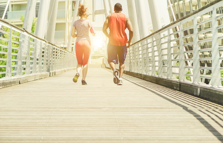 Two young athletes making jogging in a urban contest area outdoor - Runners training outdoor - Running for a sportive healthy lifestyle concept - Main focus on left shoes - Soft warm brown filter Stock Photo