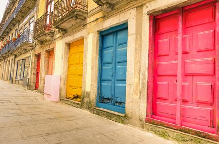 Coloridas puertas pintadas desgastadas a lo largo de la calle en Oporto - Concepto artístico de la ciudad portuguesa - mirada filtrada caliente Foto de archivo