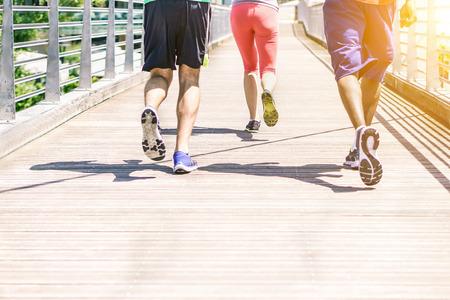 Corredores multirraciales haciendo trotar en la ciudad de concurso con la puesta de sol - Fitness personas de formación al aire libre para un estilo de vida saludable - Concepto de atleta corriendo para la competencia deportiva - Suave enfoque en centro de zapatos Foto de archivo