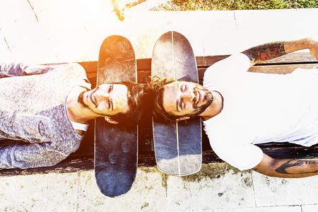 최고의 스케이트 친구 재미와 함께 웃 고 야외 - 머리 아래 스케이트 보드와 함께 하늘을 찾는 젊은 쾌활 한 사람들 - 거꾸로 포인트 - 행복 우정 개념 -