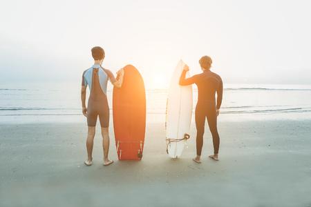 Jóvenes surfistas esperando las olas en la playa con la luz del sol en el fondo - Deporte amigos preparando buscando el horizonte listo para el surf - Extreme deporte y concepto de vacaciones - enfoque suave en ellos Foto de archivo - 72302318