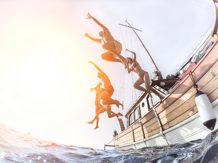 Multiracial young people diving from sailing boat into the sea - Cheerful friends having fun in summer party day - Vacation and friendship concept - Soft focus on right man - Fisheye lens distortion Фото со стока