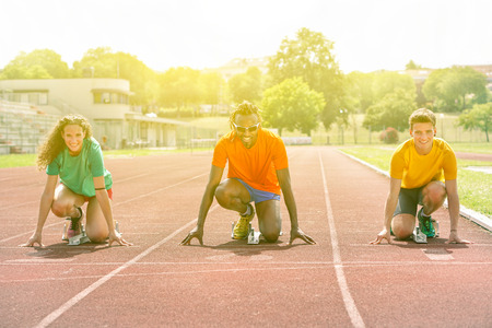 Multiracial runners at start line on track for athletic challenge  - Multi ethnic people on starting block with sunshine lights background - Competition sport concept  - Soft focus on black man Foto de archivo