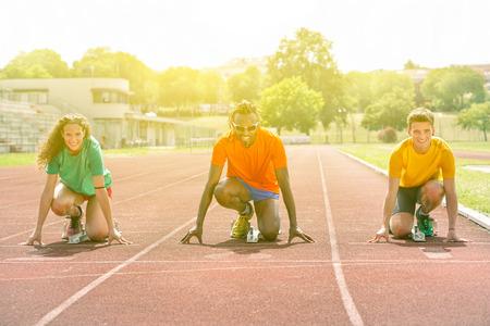 Wielorasowe biegacze na początku linii na torze dla wyzwań sportowych - Multi etnicznych osób na rozpoczęcie blok z sunshine światła tła - Konkurencja koncepcji sportu - Soft focus na czarny człowiek Zdjęcie Seryjne