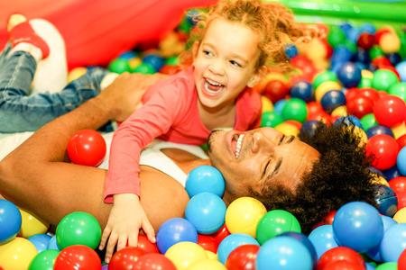 그의 딸과 함께 공을 쪼 그리고 앉는 젊은 아버지 수영장 - 행복 한 사람들이 아이 놀이터 실내 - 가족과 사랑 개념 - 소프트 포커스 남자 얼굴 - 따뜻한  스톡 콘텐츠