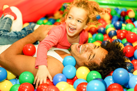 Young father playing with his daughter inside ball pit swimming pool - Happy people having fun in children playground indoor - Family and love concept - Soft focus on man face - Warm vivid filter