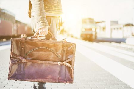 가 까이 서 기차역에서 여행을 기다리고 여행자 - 빈티지 가죽 암소를 들고 Hipster 여행자 가방 - 여행 개념 - 태양 플레어와 함께 따뜻한 빈티지 필터