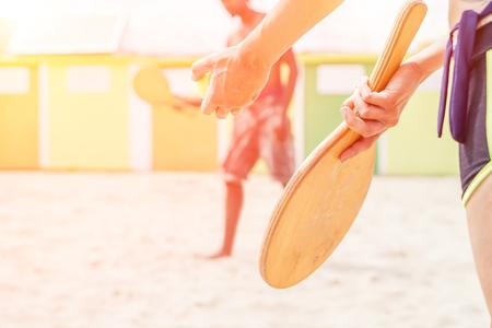 ビーチで砂にリラックスしてラケット - 夏休み楽しんで混血カップル - レクリエーションと休日コンセプト - 暖かい太陽ハロー フレア フィルターで