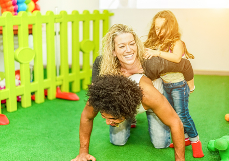 Happy multi ethnic family playing and laughing at playground kids center - Mother,father and daughter having fun in children playroom - Mixed race love concept - Focus on woman face - Warm filter
