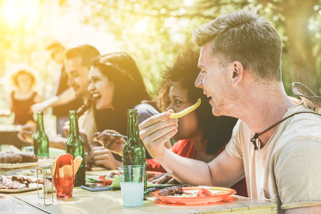 Multi ethnic people group enjoying grill meal at backyard barbecue meeting - Young friends having bbq party - Lunch and dinner concept outdoors - Soft focus on blond guy - Vintage retro filter Stock Photo