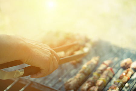 Young man cooking meat on barbecue - Chef putting some meat skewers on grill in park outdoor - Concept of eating outdoor during summer time - Soft focus on top hand - Vintage retro filter Stock Photo