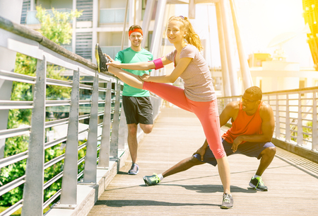 urban people: Group of friends doing stretching before jogging in a bridge outdoor - Multi ethnic fit people training in urban contest - New healthy lifestyle trend concept - Focus on girl with warm filter