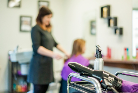 phon: Hairdresser fashion salon view with dryer and water spray with woman ready for changing color of hairstyle - Hair coiffeur dresser with one customer in her shop - Focus on water spray - Warm filter Stock Photo