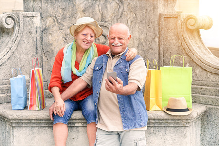 Senior couple taking selfie after shopping with smartphone - Happy tourist in the 60s having fun with new technologies outdoor - Travel lifestyle concept with retired people - Main focus on man