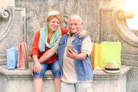 Senior pareja de tomar selfie después de las compras con smartphone - Feliz turista en los años 60 divertirse con las nuevas tecnologías al aire libre - Concepto de estilo de vida de viaje con los jubilados - El enfoque principal en el hombre