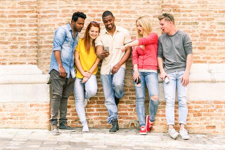Los mejores amigos de múltiples carreras ver vídeos sorprendidos en el teléfono inteligente - la gente de Yong que se divierten con los teléfonos al aire libre - Tecnología de la adicción concepto - enfoque suave en chica izquierda - filtro de la vendimia caliente saturado