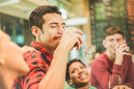 Groupe d'étudiants joyeux grillé le vin rouge au bar à vin - Les jeunes buvant l'apéritif avant le diner - Le concept de l'amitié avec les gens qui passent du temps ensemble - L'accent mis sur l'oeil de l'homme gauche Banque d'images
