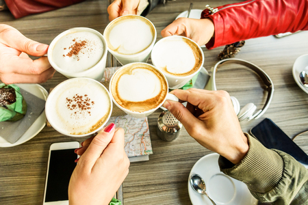 Friends group toasting cappuccino and milk with cocoa - Close up of young people drinking in coffee shop bar restaurant - Breakfast and socializing concept - Warm filter - Focus on right bottom hand