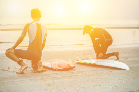 Two silhouette friends wearing swimwear with surfboards on beach with sunlight in background - Surfers preparing the boards and equipment for surfing - Extreme sport concept - Soft focus on left man Stock Photo