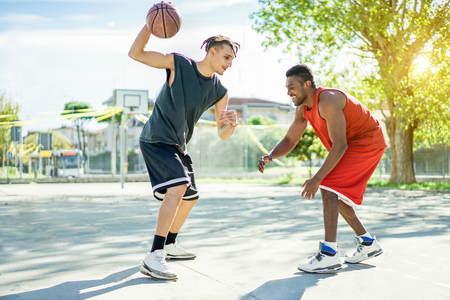 Two multiracial cheerful friends playing basketball outdoor in city urban contest with back light - Young people having fun doing sport for a healthy lifestyle - Focus on right man - Warm vivid filter