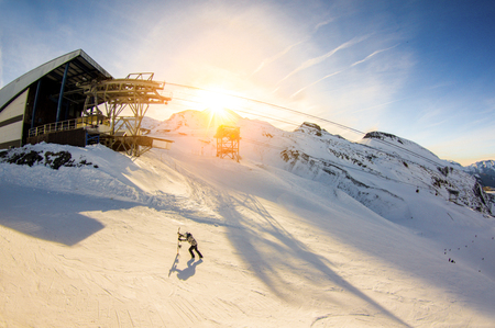 Snowboarder trying to getting at ski lift at top of the mountain with sunset in background - Panoramic wide angle fisheye view of winter snow resort - Vacation concept - Focus on man - Warm filter