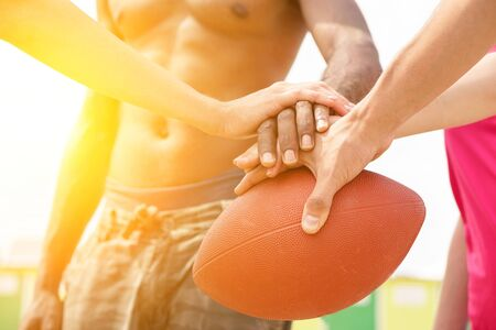 Multiracial friends playing rugby on the beach in sunny day - Multinational hands on top of oval ball - Summer sport against racism concept - Sunshine color tones with soft warm filte
