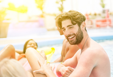 Group of friends relaxing in swimming pool party - Bearded man laughing with girl while shes lying in airbed up the water - Vacation and pool party concept - Warm vivid filter Stock Photo