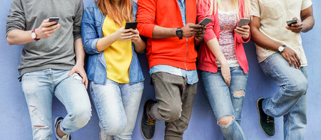 Group of multiracial students watching smart mobile phones in university break - Young people addiction to new technology trends - Alienation moment for new generation problem - Focus on center hands Фото со стока