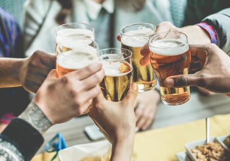 맥주를 즐기고 친구의 젊은 그룹 - 토스트와 환호 aperitif 맥주를주는 젊은 사람들이 절반 파인트 - 우정과 청소년 개념 - 따뜻한 빈티지 필터 - 하단 손 스톡 콘텐츠