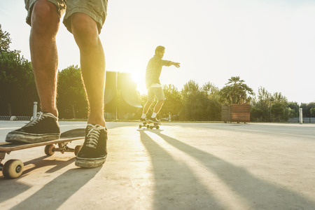 Two skaters friends training outdoor in city park at sunrise - Young people skateboarding at skate park in urban contest - Extreme sport concept - Soft focus on right silhouette man - Vintage filter Stock Photo
