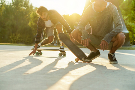 Skater friends performing with longboards in city urban park with back light- Young people having fun training skateboard extreme sport - Focus on right man feet - Warm filter with original sunlight